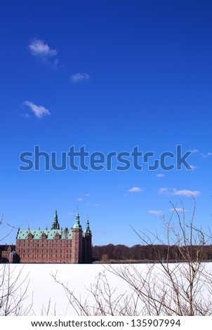The castle lake on a sunny day with blue sky and the Frederiksborg Castle in the background which is the largest Renaissance Castle in Scandinavia
