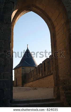 The castle of Carcassonne, France. View at a castle tower through an old stone archway in a sunny summer day. The sky is blue.