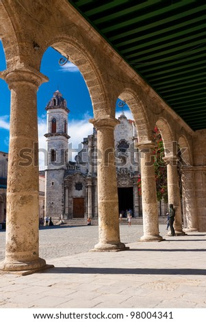 The Cathedral of Havana and its adjacent square seen through the porticoes of a nearby spanish colonial palace