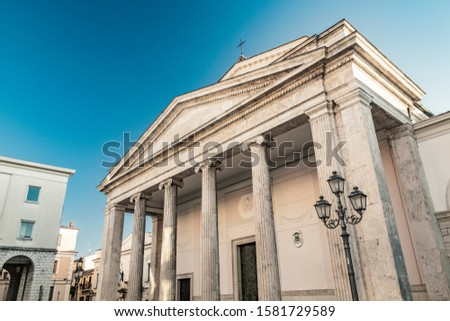 The cathedral of San Pietro Apostolo in Isernia. The facade with a large triangular tympanum in travertine, supported by pillars and columns with Ionic capitals. The portal with bas-reliefs. #1581729589