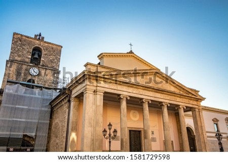 The cathedral of San Pietro Apostolo in Isernia. The facade with a large triangular tympanum in travertine, supported by pillars and columns with Ionic capitals. The portal with bas-reliefs. #1581729598