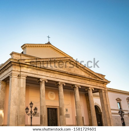 The cathedral of San Pietro Apostolo in Isernia. The facade with a large triangular tympanum in travertine, supported by pillars and columns with Ionic capitals. The portal with bas-reliefs. #1581729601