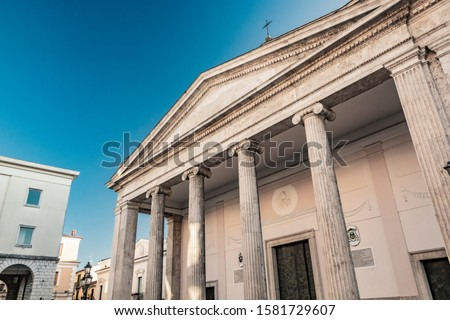 The cathedral of San Pietro Apostolo in Isernia. The facade with a large triangular tympanum in travertine, supported by pillars and columns with Ionic capitals. The portal with bas-reliefs. #1581729607