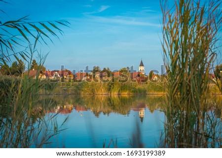 the Catholic church and its reflection on the lake Velence Stock fotó ©