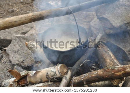 The cauldron hangs over the fire. The cauldron hangs on a stick.