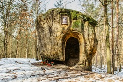 The cave and Chapel of Mary Magdalene carved in sandstone.Artworks in pine forest near Zelizy village,Czech Republic.Outdoor altar in park no people.Rural religious scenery