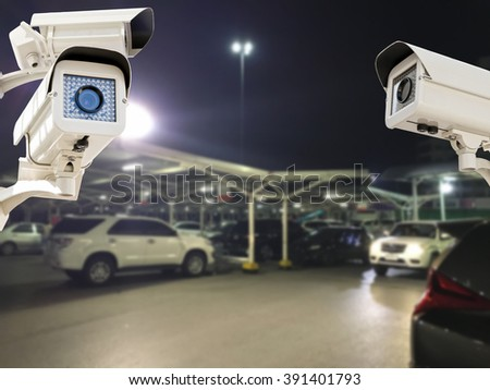 the cctv security camera operating in parking lot car at night time blur background stock photo. Black Bedroom Furniture Sets. Home Design Ideas