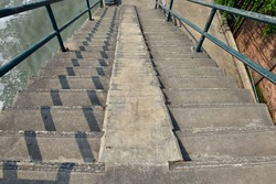 The cement stairs have a green handle leading down from the bridge over the canal.