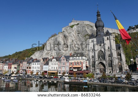 The center of the town of Dinant with the citadelle on the rock and Collegiate Church of Notre-Dame  at the Meuse river, with a Belgian flag on the right.