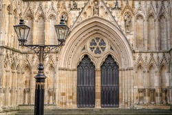 The central West facing wooden doors of York Minster set in an ornate archivolt. Twin lamps are in the foreground.