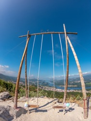 The CerLove giant wooden swing in Vila Nova de Cerveira, Portugal. The swing of the valley of Minho is next to the viewpoint of  of Cervo. People on swings admire the view.
