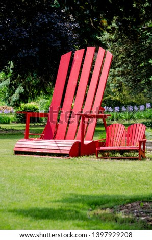 The chairs on the right are normal typical Adirondack chairs, the one on the left is a mega chair, about 10 foot tall #1397929208
