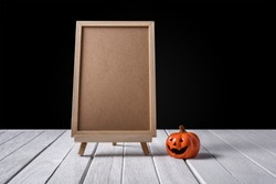 The chalkboard on the stand with Halloween Pumpkins on white wooden floor halloween background