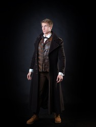 the character of the steampunk story, a young attractive man in an elegant long coat. intelligent gentleman in the Victorian style. Vintage retro suit, young attractive man in a vest and bow tie