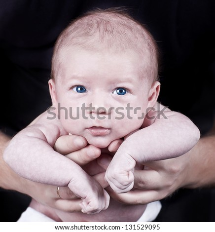 The charming baby on hands of the father on a black background