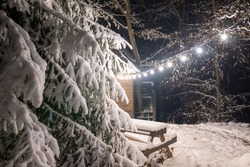 The charming view creates an incredible winter Christmas mood. A large fluffy spruce tree and a bench with a table near wooden lodge, everything covered with fluffy snow and lit by light from garlands