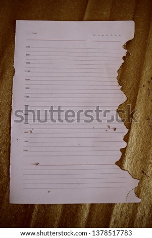 The charred sheet of paper. A sheet of paper on a gold background