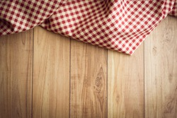the checkered tablecloth on wooden background. Use for background.