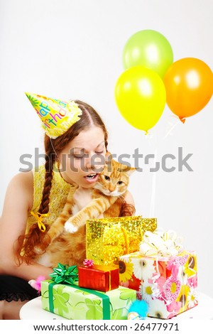 The cheerful birthday woman considers gifts with a cat in hands