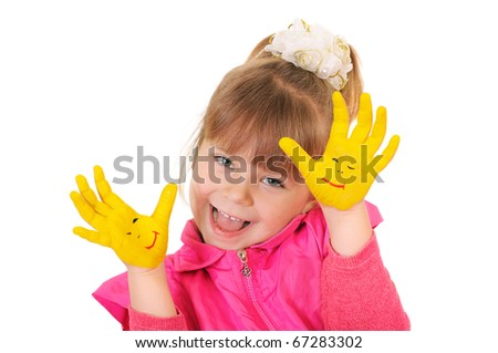 The cheerful girl keeps hands which are painted in yellow color. Isolated over white