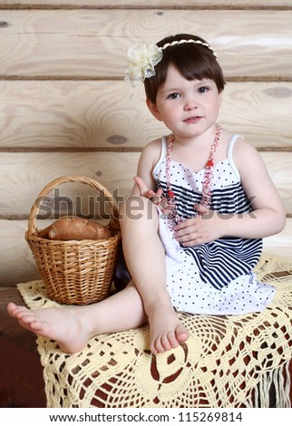the cheerful little girl and bakery products in a basket
