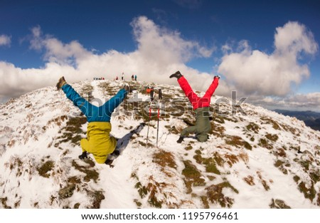 The cheerful sports people of the tourist rejoice in the autumn winter ascent to the high mountains of the Carpathians of Ukraine Petros and Goverla, standing on their heads upside down #1195796461