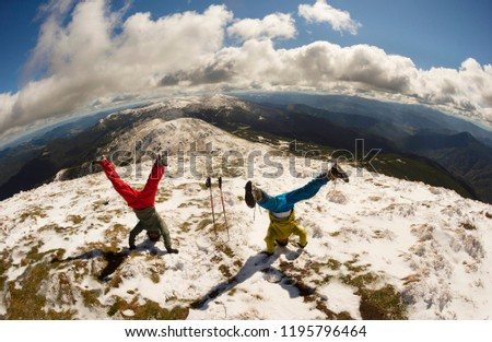 The cheerful sports people of the tourist rejoice in the autumn winter ascent to the high mountains of the Carpathians of Ukraine Petros and Goverla, standing on their heads upside down #1195796464