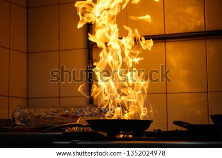 The chef cooking and makes a fire in a pan. Cooking with fire. Crown food.Flame on kitchen Foto d'archivio ©
