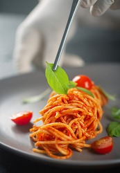 The chef decorates a haute cuisine dish with gloves with tweezers pasta in tomato sauce with basil leaves