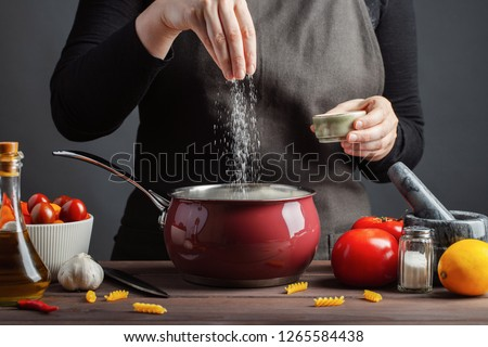 The chef preparations spaghetti and pasta, salt water, against a dark background, the concept of cooking. Woman salting water before cooking pasta fusilli