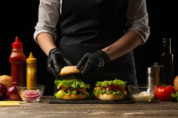 the chef prepares a burger, a hamburger. on a background with ingredients.