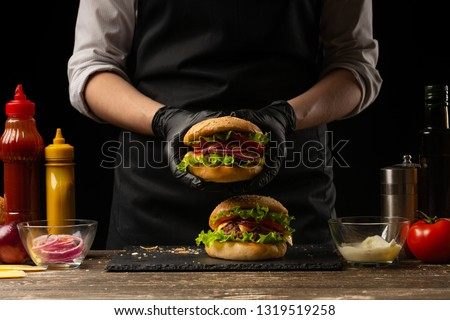 the chef prepares a burger, a hamburger. on a background with ingredients. Delicious and fast food, fast food. A menu, a cafe, fast food, catering, gastronomy