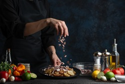 The chef prepares a dish of potatoes with octopus sprinkling with sliced octopus pieces, freezing in motion, cooking seafood dishes, gastronomy and culinary, recipe book