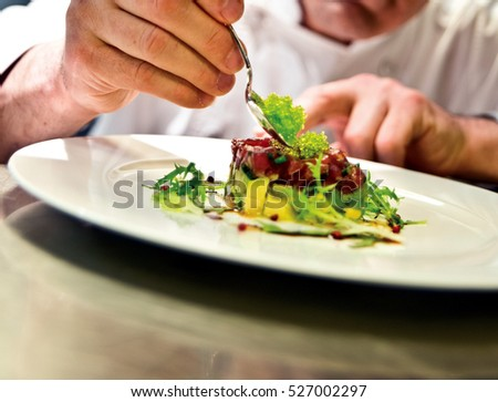 Shutterstock The chef prepares a meal. Slim subtle touches for a special presentation.