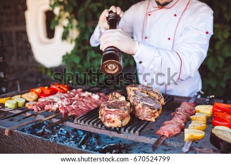 The Chef prepares meat on the barbecue. #670524799