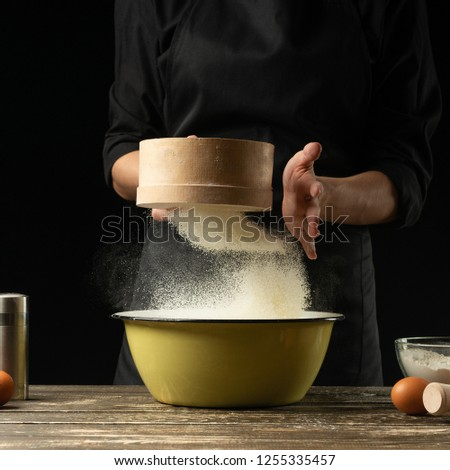 The chef prepares the dough on a dark background.Frost in the air.Preparation of delicious food, all flour