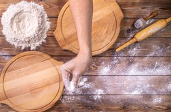 The chef's hand sprinkles wheat flour on wooden round pizza boards, chicken eggs, and a rolling pin on a brown board background. Selective focus. Preparation of food preparation. Flat layout.