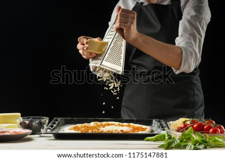 The chef sprinkles the pizza with cheese on a dark background, with free space