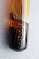 The chemical reaction of dissolution of iron in nitric acid in a test tube, with the release of brown nitrogen dioxide gas.