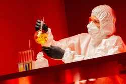 The chemist in the protective suit is removed from the bottom. A man with a test tube in a red suit. Work with dangerous substances. Lab assistant in a protective uniform.