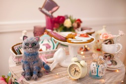 The Cheshire Cat,  a character based on the Lewis Carroll fairy tale Alice in Wonderland.  Mad tea party.