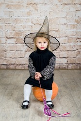 The child, a little girl in the image of the witch posing in a studio with a pumpkin and a broom on Halloween.