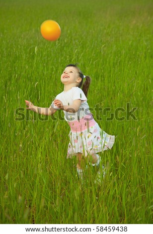 The child cheerfully plays with a ball in the field
