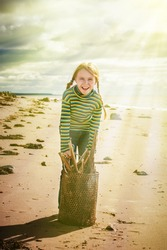 The child collecting trash in a bucket on the beach.