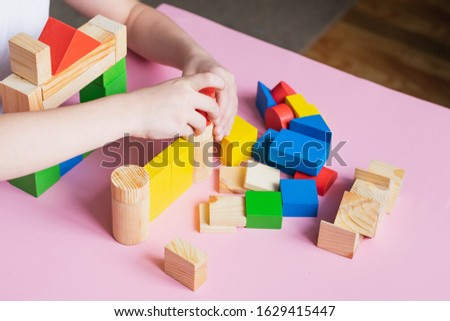 The child collects the designer builds a house of wooden cubes. Toys from environmental natural materials for children.