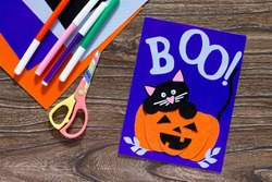 The child create a birthday card for Halloween paper black cat in pumpkin. Glue, scissors, leaves velvet paper on a wooden table. Children's art project, a craft for children. Craft for kids.