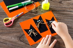 The child create a greeting card Halloween black cat out of paper, glues the paper parts. Glue, scissors, leaves velvet paper on a wooden table. Children's art project, a craft for children.