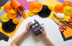 The child creates a gift box of a black cat. A party for Halloween. Children's hands make a master class. Craft for kids. Materials for creativity of orange, purple and black colors. School, education