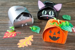 The child creates a gift box of a black cat of Halloween, a Halloween pumpkin and a vampire box. Children's art project, craft for children. Craft for kids.