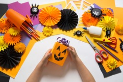 The child creates a hand-crafted pumpkin. Children's hands. Gift box for a party of Halloween. Craft for kids. Education school kindergarten. Pumpkin made of paper. Materials for creativity.